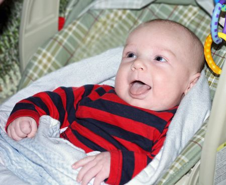 Baby sitting in a carrier laughing Stock Photo