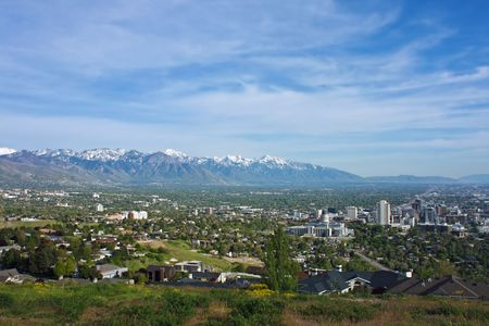 pioneers: Salt Lake City on a sunny day with view of downtown and residential area and mountains in the distance