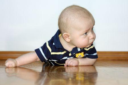 Baby boy laying on tummy on wood floor
