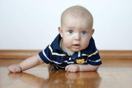 Cute baby boy laying on his tummy on a hardwood floor Stock Photo - 7470485