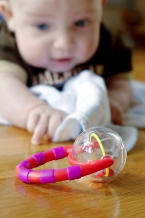 Baby boy reaching for a toy rattle in the foreground Stock Photo