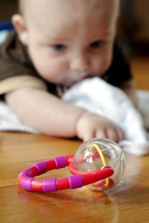 Baby boy reaching for a toy rattle in the foreground Banco de Imagens