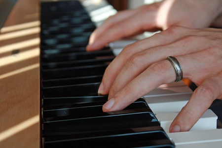 recite: Closeup of fingers playing the piano Stock Photo