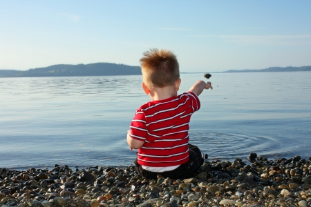 Blond toddler boy sitting on pebbly beach throwing rocks in the water Stock Photo