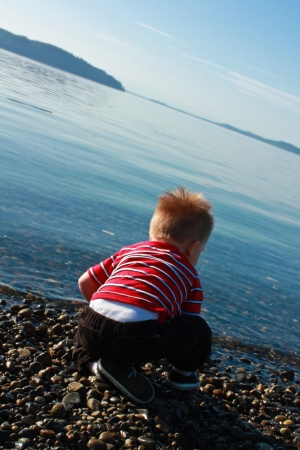 Blond toddler boy sitting on pebbly beach looking toward the water Stock Photo