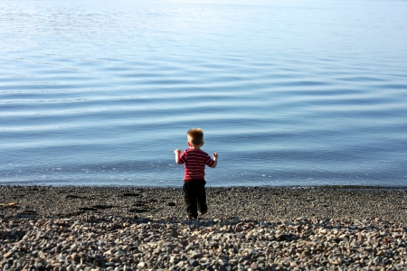 Blond toddler boy running along a pebbly beach toward the water