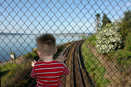 Toddler boy standing on a bridge behind a wire fence waiting for the train