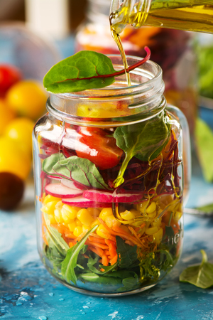 gass: Diet or health food concept: veggies salad in mason jars over bright blue background. Selective focus Stock Photo