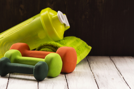 Family sport or weight loss concept. Dumbbells, towel and shaker. Toned image, selective focus