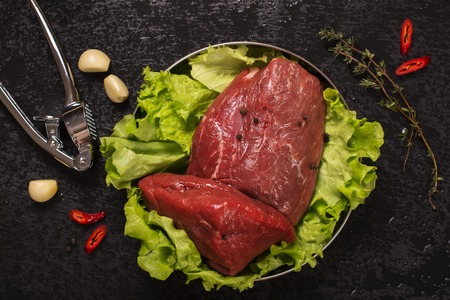source of iron: Raw meat with lettuce, garlic, chili peper and thyme over black stone table. Top view