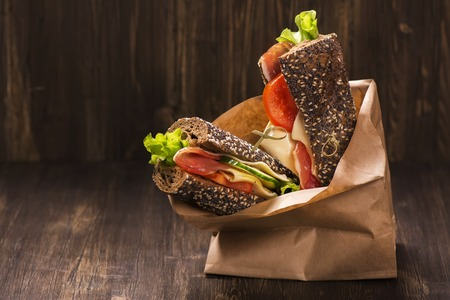 Rye bread sandwiches with ham, cheese and vegetables in a craft paper bag. Take away food. Selective focus Stock fotó