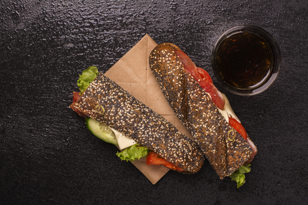Rye bread sandwiches and glass of cola over black stone background. Top view