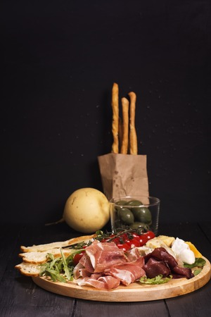 grissini: Various types of italian appetizers: ham, cheese, grissini, olives, fruits over black wooden background. Selective focus Stock Photo