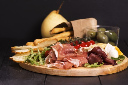 さまざまなイタリアの前菜: ハム、チーズ、グリッシーニ、オリーブ、ブラックの木製の背景の上の果物。選択と集中