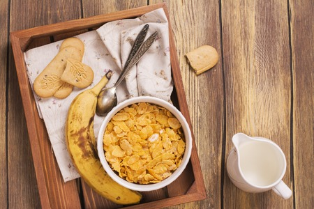 adding: Tasty and healthy breakfast on wooden tray. Female hand holding jar and adding milk into the bowl. Top view.