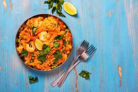 Traditional spanish paella dish with seafood, peas, rice and chicken over grunge blue background. Top view. Selective focus Archivio Fotografico