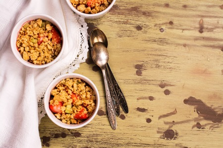 rheum: Crumble with strawberry, oat and rhubarb over wooden table. Top view Stock Photo