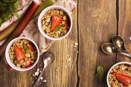 rheum: Crumble with strawberry, oat and rhubarb over wooden table. Top view. Copy space Stock Photo