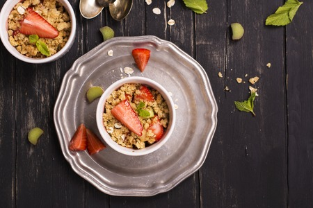 rheum: Crumble with strawberry, oatmeal and rhubarb over vintage black wooden table. Top view