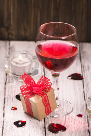 wine gift: Valentines day card with glass of pink wine, gift box, hearts and candles Stock Photo