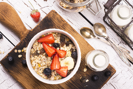 healthy foods: Homemade granola with fruits, berries and milk over wooden background. Rustic style. Top view. Space for text Stock Photo
