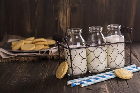 Bouteilles de lait dans un panier en fil vintage et tas de biscuits sur fond en bois. Style rustique Mise au point sélective
