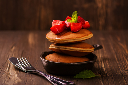Stack of pancakes with fresh strawberry, honey and mint in frying pan. Selective focus