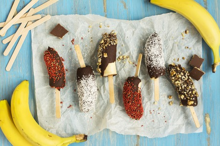 Frozen homemade banana pops covered with chocolate, sprinkles, nuts and coconut chips. Top view Archivio Fotografico