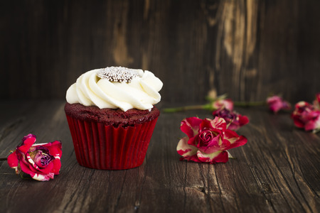red velvet cupcake: Red velvet cupcake and roses buds over grunge wooden background. Selective focus Stock Photo