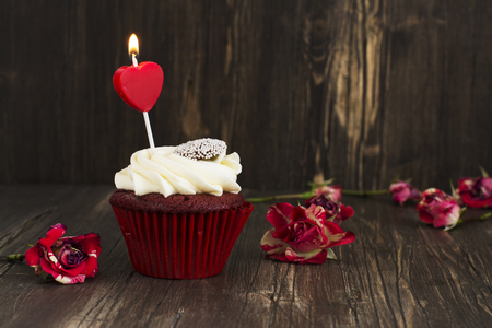 red velvet cupcake: Delicious red velvet cupcake with burning candle. Anniversary, valentines day greeting card. Toned image. Selective focus