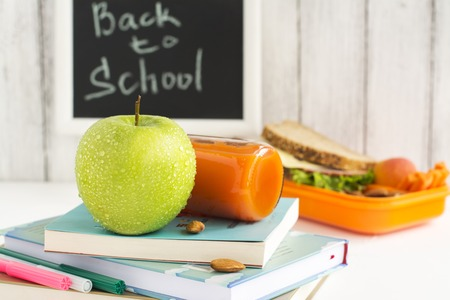 dinnertime: Back to school concept, lunchbox, apple and carrot juice. Selective focus