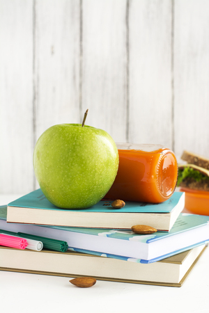 dinnertime: School lunchbox: healthy food, fruits, books and apple over white table. Selective focus
