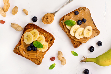 Peanut butter sandwiches with bananas and blueberry. Top view. Space for text Reklamní fotografie