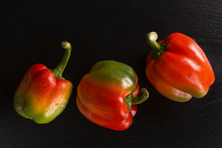 bell peper: Three red green yellow pepper bells on black stone background. Top view. Space for text Stock Photo