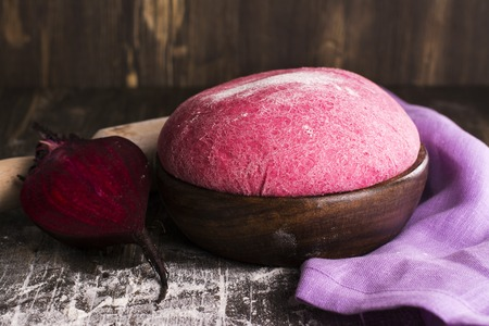 colored backgound: Pink beet dough and ingredients over wooden table. Selective focus. Vintage style