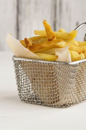 frites: French fries in metal wire basket over white kitchen table. Selective focus Stock Photo