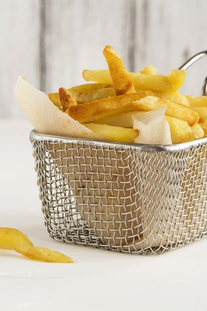 French fries in metal wire basket over white kitchen table. Selective focus Stock Photo