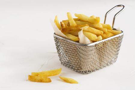 白いキッチンのテーブルの上の金属ワイヤー バスケットのフライド ポテト。選択と集中