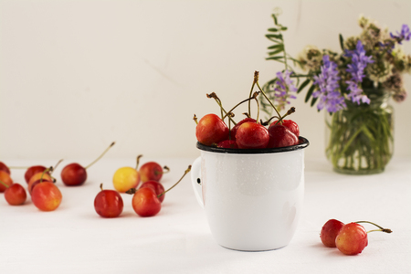 Summer composition - sweet cherries and field flowers over white background. Natural light. Selective focus