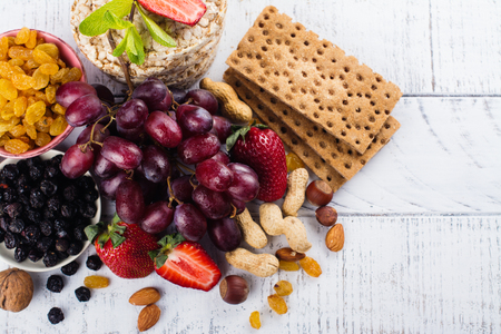 containing: Healthy snacks: dry and fresh fruits, healthy breads, berries and nuts on white wooden table. Copy space
