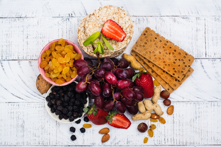 Healthy snacks: dry and fresh fruits, healthy breads, berries and nuts on white wooden table. Copy space