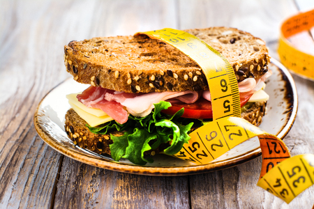 Delicious sandwich with measure tape on wooden table. Healthy eating or diet concept Stock Photo