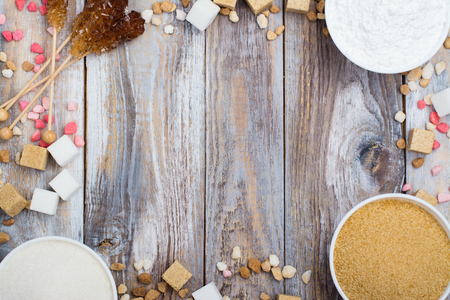 Assortment of different types of sugar on wooden table. Space for text