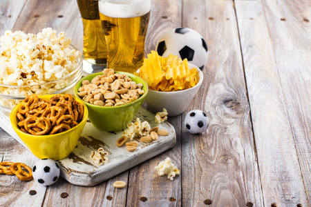 Beer and snacks on wooden table. Football season or fans party concept