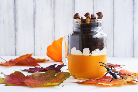 jello: Layered halloween dessert with pumpkin jello, cream and chocolate cookies in glass jars on autumn background. Selective foucs