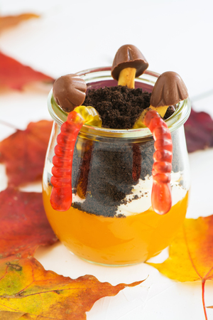 Layered halloween trifle with pumpkin jello, worms and toadstools on autumn background. Kids dessert. Selective focus