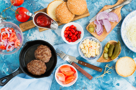 Preparing homemade burgers with beef cutlets, hot spicy scrambled eggs and vegetables. Top view. Space for text