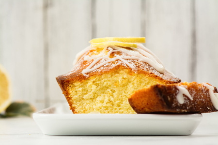 Lemon loaf cake with white glaze and lemon slices. Selective focus. Space for text