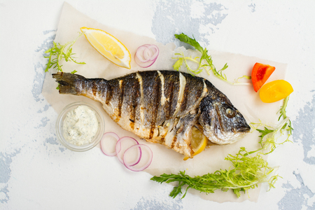 Delicious grilled dorado with vegetables and tartar sauce overs white stone table. Space for text Stock Photo