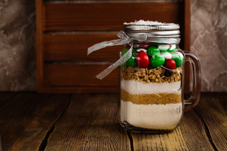Cookies mix with color candies in a jar with paper tags. Handmade Christmas gift over dark stone background. Selective focus